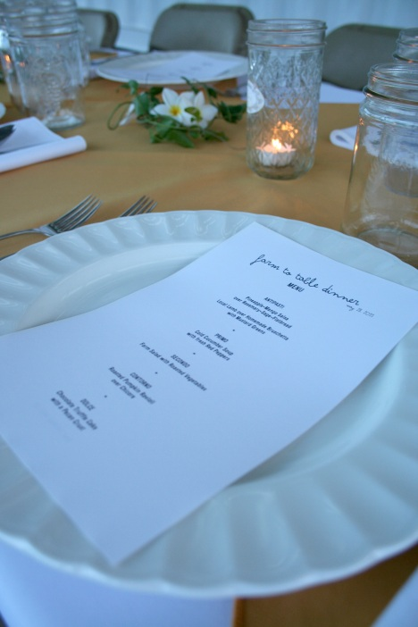 A menu rests on a plate of a formally set table with flowers, vines and candles.