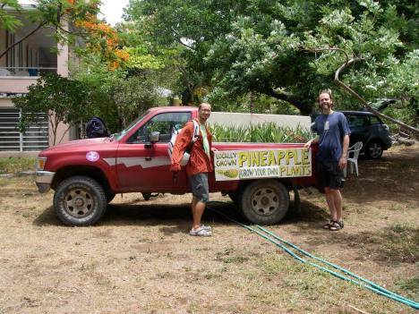 "Luca Gasperi and Eric Ogden in 2008 with our red pickup truck holding the ""Grow Your Own Pineapples"" sign, on our way to Mango Melee!"