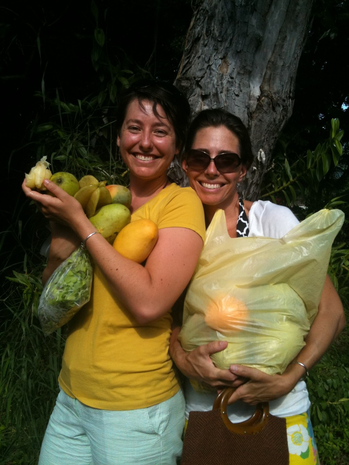 Two happy ladies laden down with microgreens and mangoes at the ARTfarm