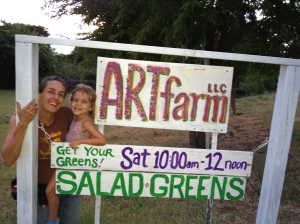 "Happy ARTfarm mom and kid with the ARTfarm sign. ""Get Your Greens!"""