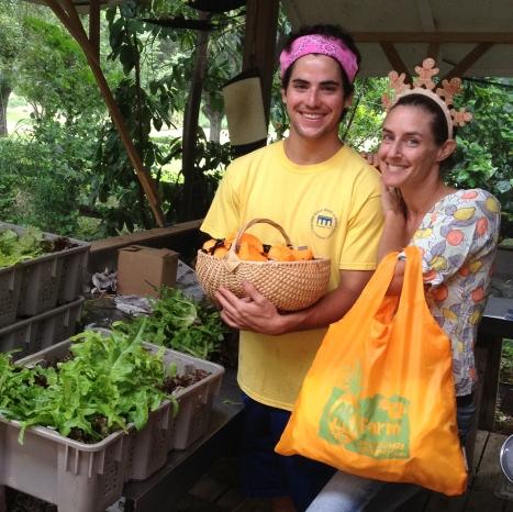 Two happy people at ARTfarm showing off the new reusable shopping bags in front of crates full of fresh lettuce heads.