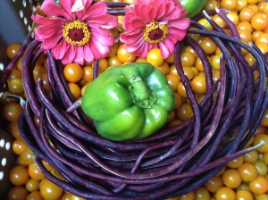A happy face on a bed of orange sungold cherry tomatoes is made from pink zinnia flower eyes, a sweet green pepper nose, and purple long bean smile.