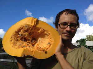 A farmer holds a half pumpkin