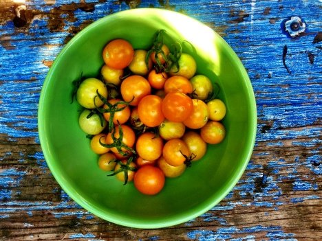 A green ceramic bowl holds a generous handful of vine-ripe cherry tomatoes in yellows and oranges, sitting on a worn wooden board with blue fading paint.
