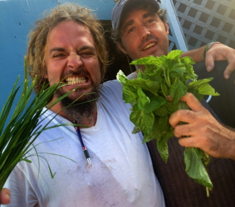 Two chefs making pirate faces hold up bunches of fresh green herbs from ARTfarm at Savant Restaurant in Christiansted, St. Croix USVI.