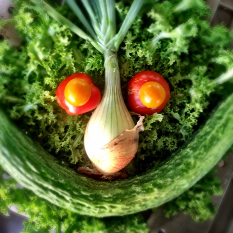 A face made of vegetables; frilly endive forms the round face with an onion with its top for a nose and eyebrows, a big cucumber smile, and slicer and cherry tomatoes stacked up as the eyes.