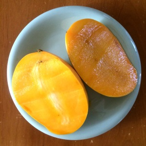 A yellow mango halved on a blue plate.