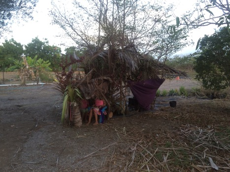 Two kids hang out in a grass hut they made from dead coconut trees, victims of the drought.