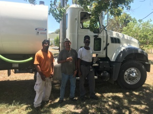 Three equipment operators with a new tanker truck.